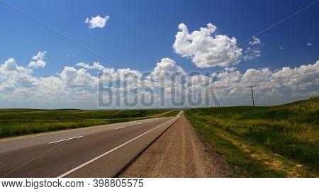 Road Trip In The Prairies: Wide Open Prairie With Paved Highway Vanishing In The Horizon