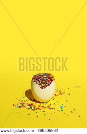 White Egg Shell With Colorful Candies Over Yellow Background.  Easter, Holidays, Food Concept. Absta