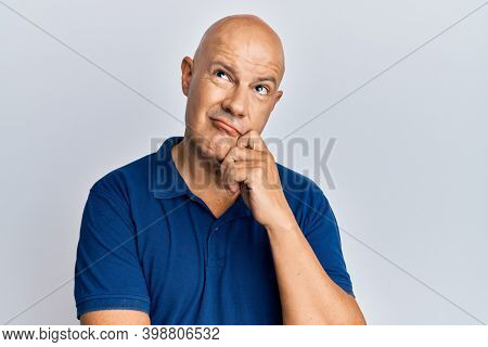 Middle age bald man wearing casual clothes thinking concentrated about doubt with finger on chin and looking up wondering
