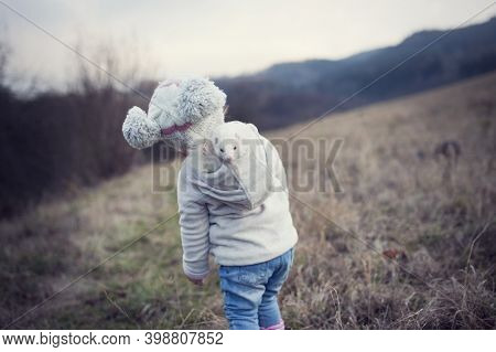 A Little Girl Is Outside With Her Pet. Cute Baby Girl Wearing A Ferret In A Hood. The Child And His
