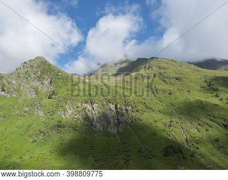 View On Green Mountain Peaks With Water Streams From Melting Snow, Summer Sunny Day, Blue Sky White
