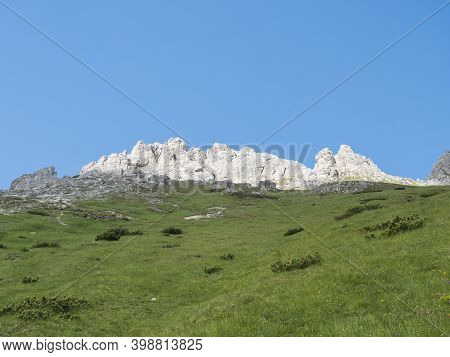 View On White Shining Limestone Moutain Peaks And Rock With Green Grass And Clear Blue Sky. Alpine L