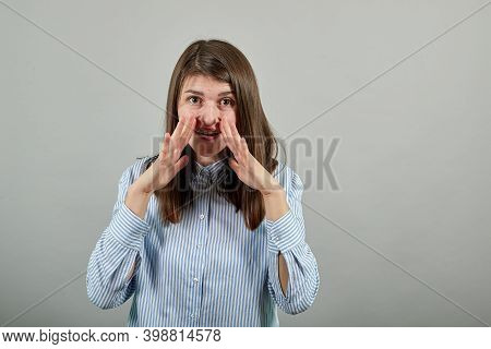Scream And Shout Holding Hands Near Opened Mouth. Screaming Loudly With Hand At Face. Cupping. Yelli