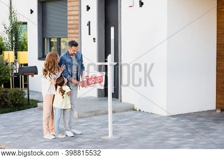 Full Length Of Positive Husband Holding Sign With Sold Lettering While Standing With Wife And Daught