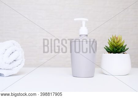 Gray Soap Dispenser, White Towel And Potted Plant For Spa, Body And Face Care, Bathroom Interior In