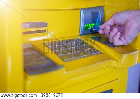 Man's Hand Inserting A Credit Card In Atm , Hand Inserting Atm Plastic Card Into Bank Machine To Wit
