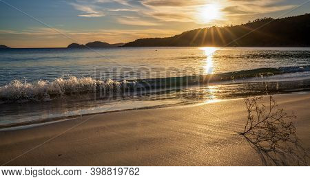 A Beautiful And Calm Golden Sand Beach With Small Waves Lapping At The Shore And Driftwood Coral At