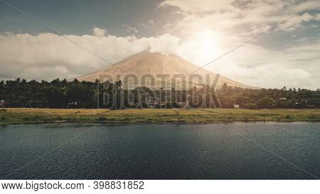 Volcano erupt at sun shine over lake shore aerial. Philippine coutryside of Legazpi town at green valley with palm trees. Rural cottages at exotic forest. Cinematic nobody nature landscape at sunlight