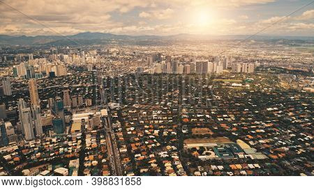 Sun metropolis city with streets, roads aerial. Downtown buildings, skyscrapers at summer sunny day. Cinematic cityscape of Manila town, Philippines, Asia
