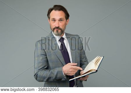 Dedicated To Study. Teacher Point Finger At Open Study Book. Back To School Supplies. Formal Educati