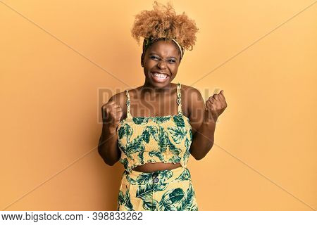 Young african woman with afro hair wearing summer dress excited for success with arms raised and eyes closed celebrating victory smiling. winner concept.