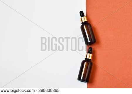Two Dropper Oil Bottles. Serum Oil In Glass Bottles With A Dropper On A Pink-white Background. Natur