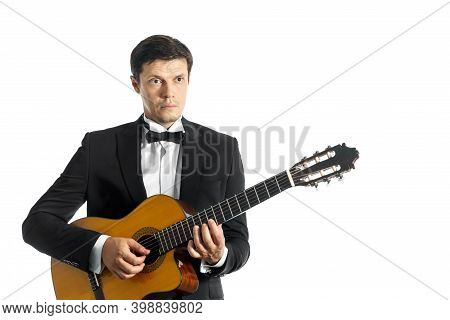 Young Man In Black Classic Suit With Bow Tie Posing With Classical Guitar In Studio On White Backgro