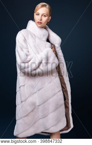 Fur coat style. Fashionable model in an expensive white mink fur coat on a dark blue background.