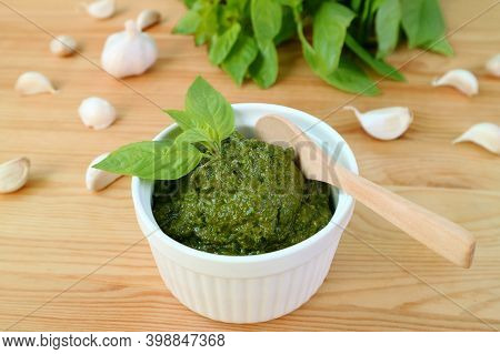Tasty And Healthy Homemade Fresh Basil Pesto Sauce In White Bowl With A Wooden Spoon