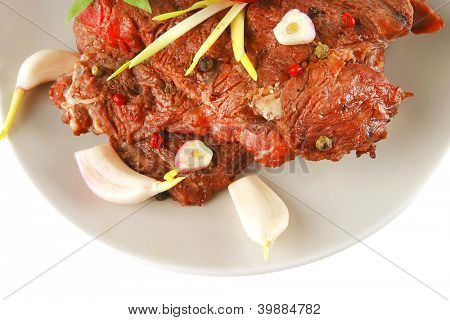 served beef on grey dish with gralic and pepper