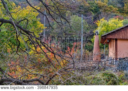 Gongju, South Korea; October 29, 2020: Smoke Coming From Tall Stucco Outdoor Incinerator Behind Hous