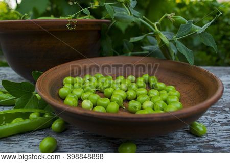 Green Peas Peeled And Not Peeled In Pottery Close-up. Green Peas In Clay Pots On A Wooden Table