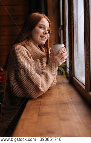Portrait Of Charming Smiling Young Woman Standing Near Window With Cup Hot Coffee And Looking Out. S