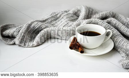 Cup Of Coffee With Cinnamon Sticks And Anise Star On White Background. Sweater Around. Winter Mornin