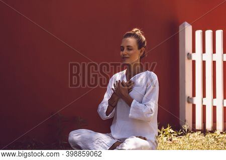 Beautiful Peaceful Female Doing Yoga Exercises in the Backyard. Morning Meditation in Lotus Posture. Healthy Zen Lifestyle
