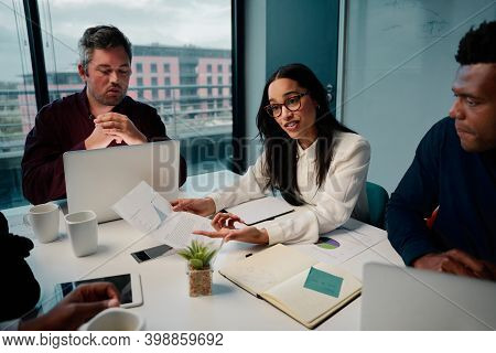 Young Smart African American Businesswoman Showing A Graph To Her Multiethnic Male Colleagues In A M