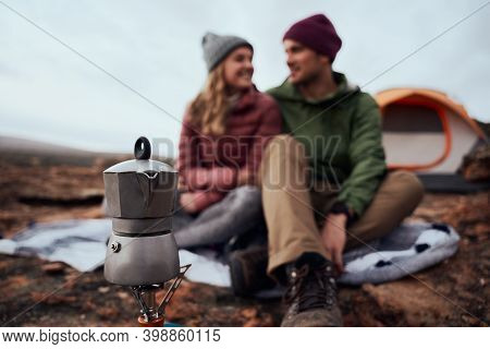Closeup Of Kettle On Gas Stove During Camping With Smiling Couple Looking At Each Other During Winte