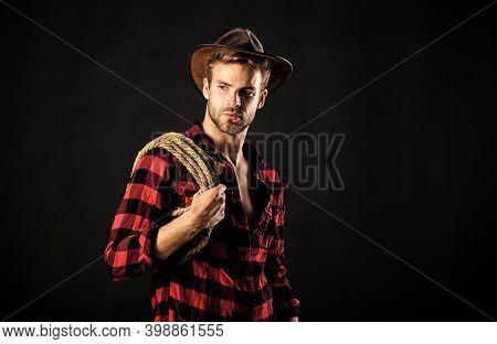 Western Life. Lassoing On Prairie. Man Unshaven Cowboy Black Background. Cowboy Wearing Hat Hold Rop