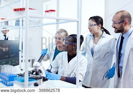 Group Of Multiethnic Pharmacy Scientists In Lab Coats Working Together In Modern Facility. Black Hea