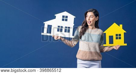 Happy Young Smiling Asian Woman Choosing Difference Two House Mockup Paper On Blue Color Background,