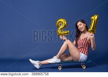 Happy Young Asian Woman Sitting On Surfskate Or Skateboard And Holding 21 Gold Color Balloons For Ce