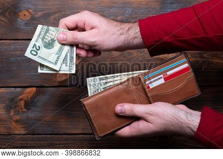Wallet With Dollars In Men Hands. Wallet With Money And Credit Cards On A Wooden Background.