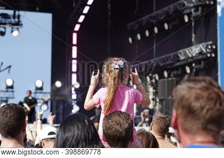 Moscow, Russia - September 07, 2019: Back View Of Little Girl Sitting On Parent's Shoulders And Show