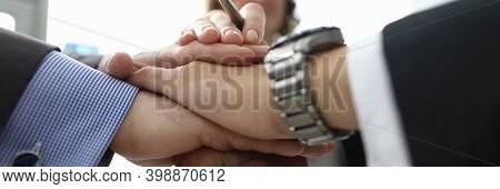 Businesswoman And Two Businessmen Folded Their Hands Together In Office Closeup. Conclusion Of Inter