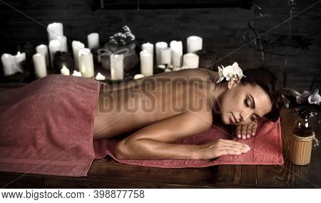 Massage woman back in beauty spa with candlelight. Eyes closed, orchid flower in head for lying down female on table.
