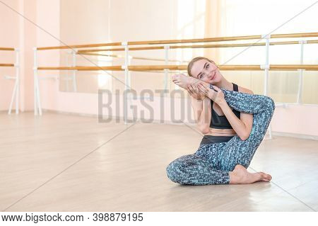 Very Flexible Caucasian Woman Doing Stretching Exercises In Dance Class With Mirrors And Barre.
