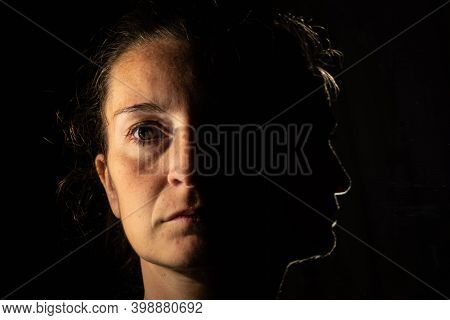 Dark Portrait Of A Serious Woman With Only Half An Illuminated Face On A Black Background That Is Un