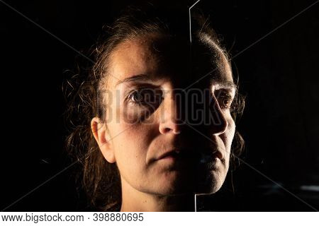 Dark Portrait Of A Serious Woman With Only Half Her Face Illuminated On A Black Background That Is U