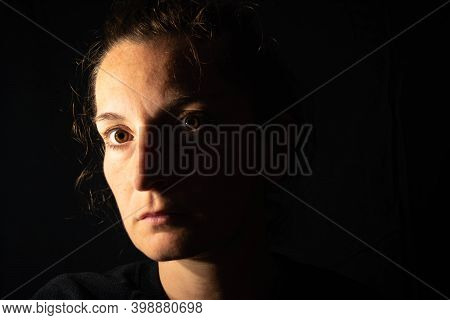 Dark Portrait Of A Serious Woman With Her Face Partially Lit. The Woman Is Staring Blankly Showing S