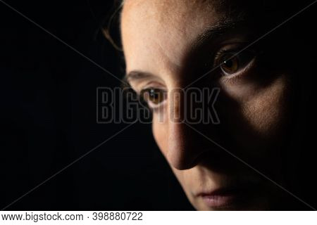 Close-up Of A Dark Portrait Of A Very Dimly Lit Woman. The Woman Is Looking At Infinity, Transmittin