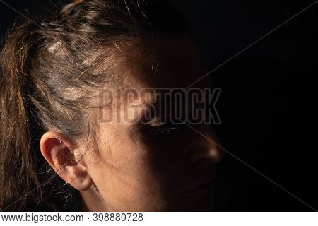 Close-up Of A Dark Portrait Of A Very Dimly Lit Woman. The Woman Has Her Eyes Downcast And Conveys F