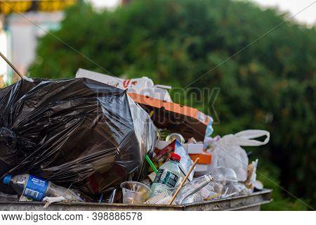 Dnepr, Ukraine- September 12, 2020: Overflowing Dirty Street Garbage Bin With Plastic Ware, Containe