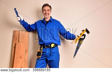 Parquet Assembler In Overalls Smiling With Tools In Hands Leaning On Parquet Slats In A Room. Horizo