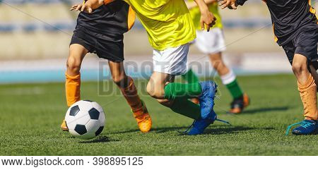 Children Soccer Players In A Football Duel Running After Ball On A Game. Sports Stadium In The Backg