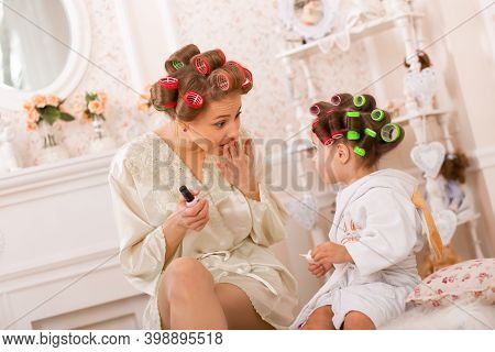 Adorable Little Girl With Her Mother In Curlers Paint Their Fingernails. Copies Mom's Behavior. Mom