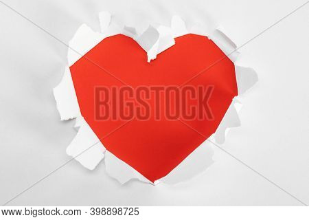 Torn white paper heart over red background with copy space for text, Valentine's day love concept