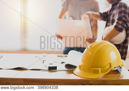 Construction Safety Helmets On Table With Engineer Holding Blueprint Background
