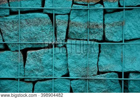 Stone Gabion Wall Sprayed With Street Vandal, Vandalism. Street Turquoise Silver And Purple Overlap