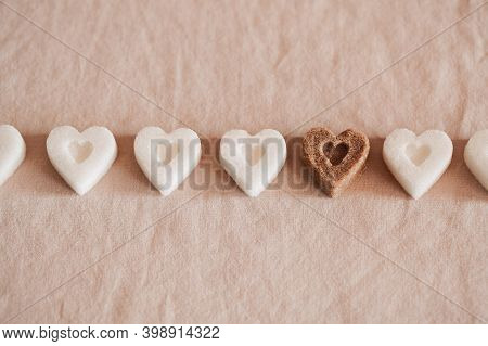 White Heart Shaped Sugar And One Brown On Pink Textile Background. Valentines Day Concept