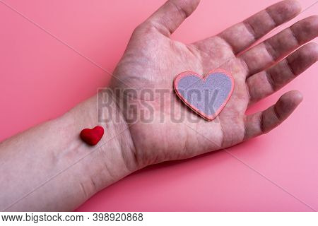 Man Holds A Red Heart In His Palms On A Pink Background
